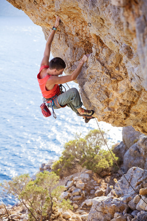 Young man lead climbing on overhanging cliff on coast, Kalymnos island, Greece