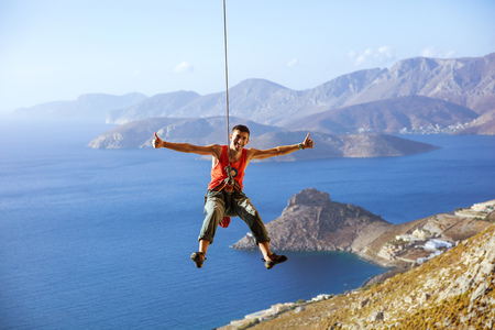 Cheerful rock climber swinging on rope and showing thumbs up against view of coast