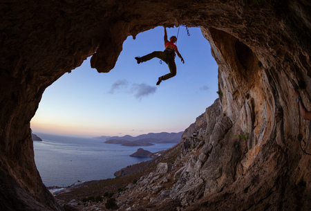 Female rock climber gripping handhold on ceiling in cave Stock Photo