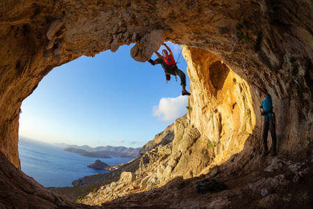Rock climbers: one man lead climbing on ceiling in cave, another belaying
