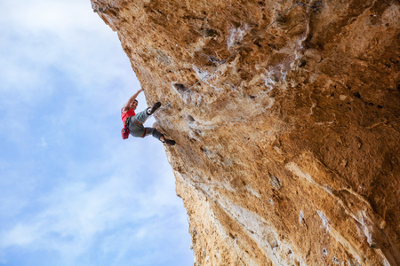 overhanging: Smiling rock climber on overhanging cliff, view from beneath Stock Photo
