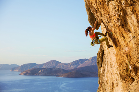 Female rock climber on challenging route on cliff, view of coast below Stock Photo