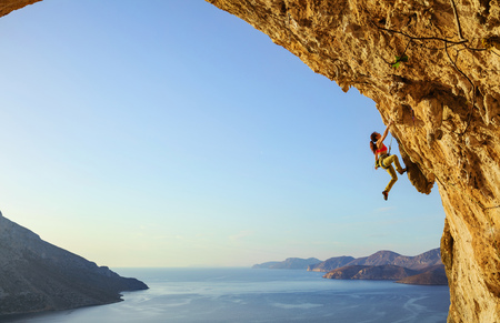 Young woman climbing challenging route in cave at sunset, Kalymnos island, Greece Stock Photo