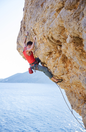 overhanging: Young man lead climbing on overhanging cliff over sea