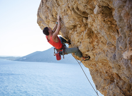overhanging: Young man lead climbing on overhanging cliff over water Stock Photo