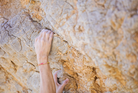 Closeup of climbers hands on cliff Stock Photo