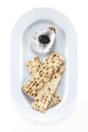 matzah: Black sturgeon caviar and matzah on plate, view from above. With clipping path.