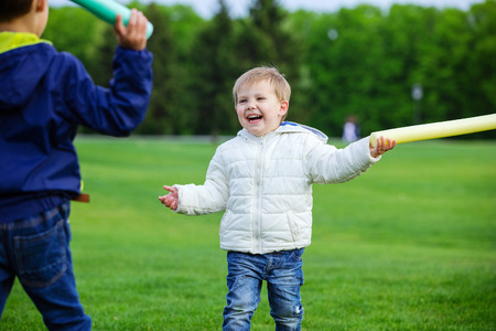 Two brothers playing with toy swords and laughing in park Stock Photo