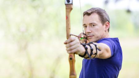 bowman: Bowman aiming arrow at target, image with selective focus
