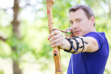 bowman: Bowman aiming arrow at target, image with shallow depth of field, left hand and bow in focus