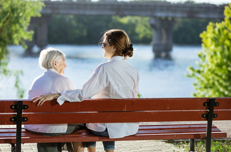senior adult woman: Senior woman and her adult granddaughter sitting on bench in summer park and talking