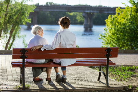 senior adult woman: Senior woman and her adult granddaughter sitting on bench in summer park
