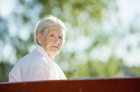aged: Senior woman sitting on bench in summer park