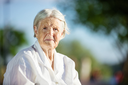 aged: Portrait of senior woman sitting on bench in park Stock Photo