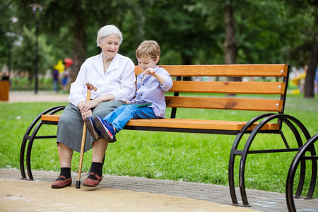 Young boy and his great grandmother using tablet while sitting on bench in park