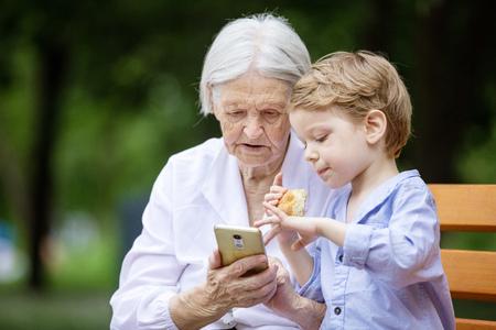 Joven y su gran abuela utilizando teléfono inteligente mientras estaba sentado en el banco en el parque
