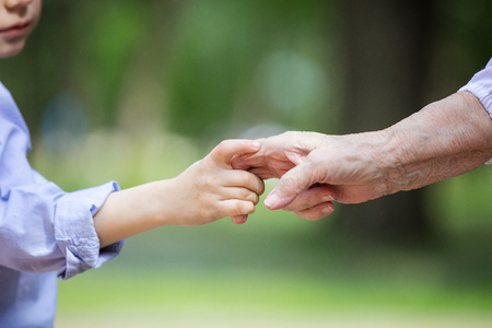 Cropped view of young boy holding great grandmother's hand outdoors