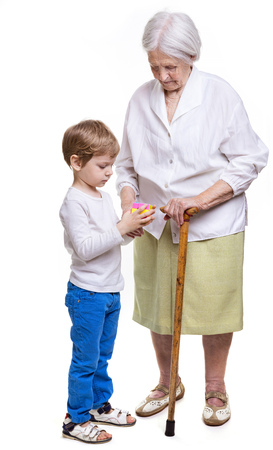 Young boy and his great grandmother trying to solve cube puzzle over white background Stock Photo