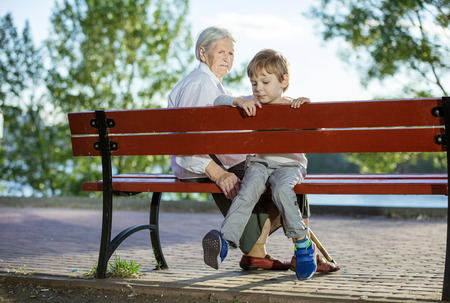 grandkids: Senior woman and great grandson sitting on bench in summer park