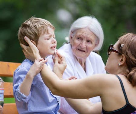 treating: Mother treating scrape on sons chin while sitting on bench in park. Senior grandmother sitting beside on bench.
