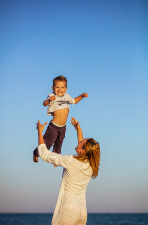 Happy young woman throwing little son up in air, family having fun on beach