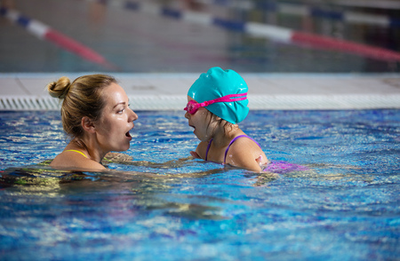 Mother or instructor teaching little girl to hold breath before diving in pool Stock Photo