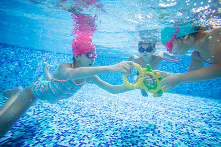 Kids swimming underwater and playing with toys in swimming pool