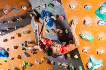 Young man bouldering in indoor climbing gym, trying to solver challenging problem