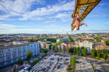 Urban climbing: rock climber hanging upside down on jib of construction crane. Panoramic view of city at background. Stock Photo