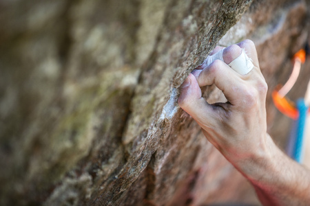 Rock climbers hand gripping small hold on natural cliff, closeup view