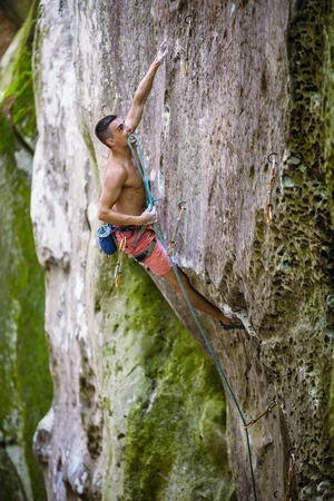 Rock climber holding rope with teeth before making clip on natural cliff Stock Photo
