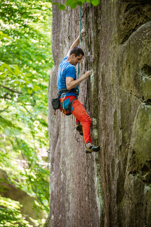 Young male rock climber on challenging route on vertical cliff