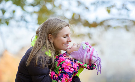 Young mother and daughter having fun in autumn park