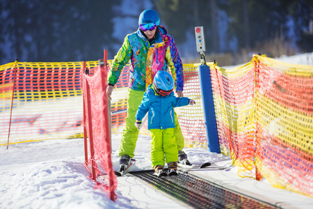 kids at the ski lift: Young boy and his father stepping on travelator in childrens area on skiing resort