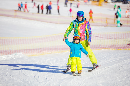 kids at the ski lift: Father ior instructor teaching little boy to ski in childrens area on winter resort