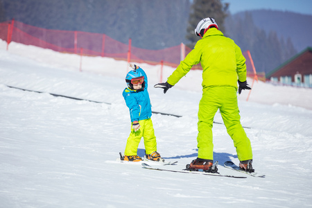 kids at the ski lift: Lesson at skiing school: instructor teaching little skier how to make turns, young boy doing exercise on slope in childrens area Stock Photo