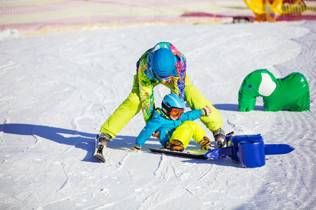 kids at the ski lift: Father helping little get on feet after fall on ski slope. Childrens area on winter resort, students should slide past toy obstacles. Stock Photo