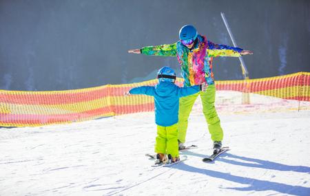 kids at the ski lift: Father or instructor teaching little boy to ski. Ski slope on winter resort.