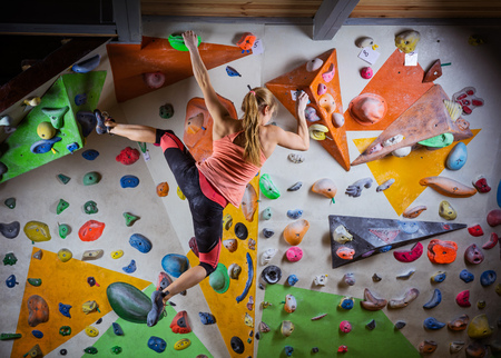 Young woman bouldering on overhanging wall in indoor climbing gym
