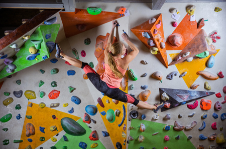 Young woman bouldering on overhanging wall in indoor climbing gym, doing splits to reach next handhold
