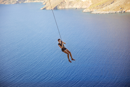 Young woman wearing safety harness swinging on rope against view of coast below Stock Photo