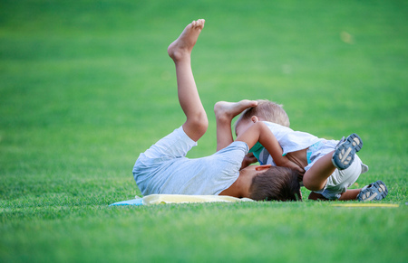 Two boys fighting outdoors. Siblings wrestling on grass in summer park. Siblings rivalry. Stock Photo