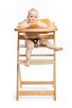 Cute baby girl eating peach and smiling while sitting in high chair over white