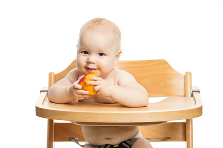Cute baby girl eating peach while sitting in high chair over white background