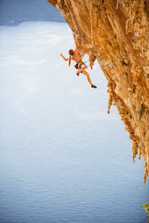 Young female rock climber in bikini hanging with one hand on overhanging cliff