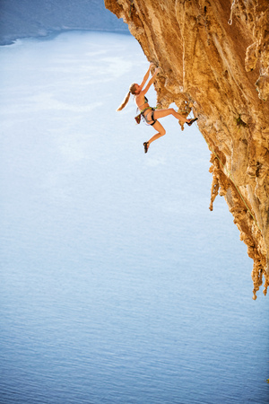 Young female rock climber wearing bikini on challenging route on cliff Stock Photo