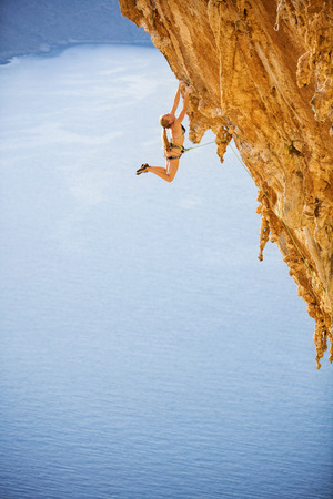 Female rock climber jumping on handholds on challenging route on cliff, Kalymnos island, Greece