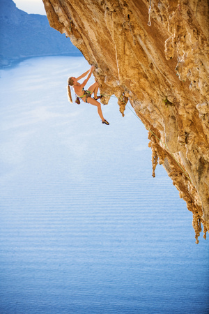 Young female rock climber on challenging route on cliff, view of sea and coast below