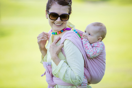 Cheerful Caucasian woman carrying her baby daughter on back outdoors in spring park