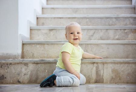 Baby girl at bottom of stairs outdoors, looking at camera and smiling Foto de archivo